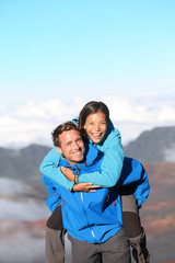 Hiking couple piggybacking happy