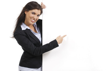 Junge hübsche Frau zeigt auf leeres Plakat