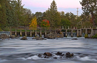 Autumn colors on river spillway at sunset HDR