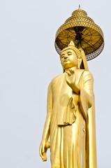 Golden buddha statue with grey sky
