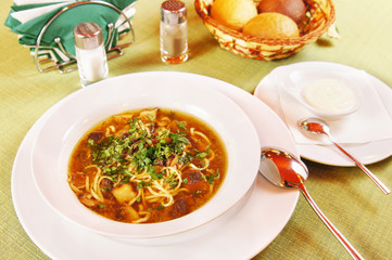 Soup with noodles and mushrooms in a plate
