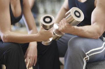 A man and woman working out at the gym with dumbbell weights