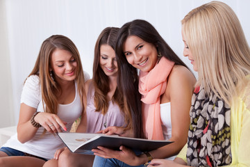 Four female friends looking at a folder