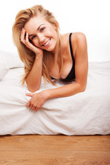 Sexy smiling blonde on her bed