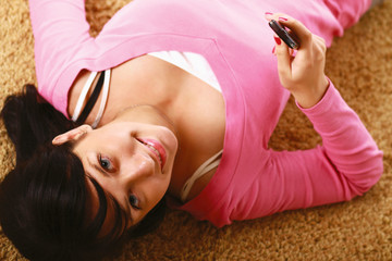 Woman holding a phone, lying on the carpet