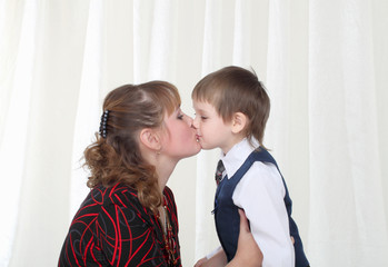 Little son in smart suit kissing his mother