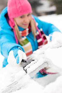 Woman brushing snow from car windscreen winter