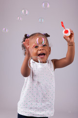 Little African American girl playing with soap bubbles