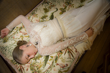 Beautiful young woman dressed in clothes of epoch slept in the c