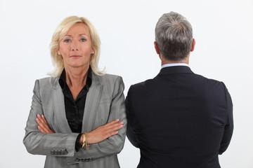 Smart mature businesswoman next to businessman