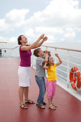 Mother with her childrens launch kite from deck of ship