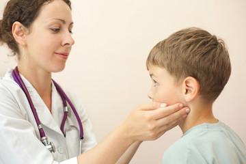 Doctor checks little boy lymph nodes, focus on boy