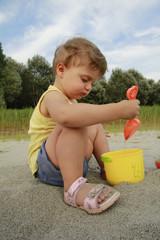 Bambina paletta sabbia gioco secchiello