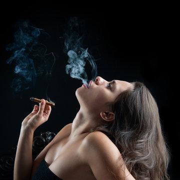 Woman smoking cigar against dark background. Fashion photo