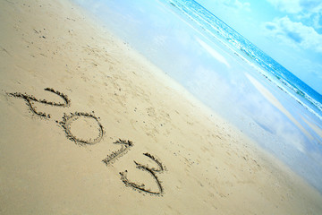 "New year background of beach with ""2013"" drawn in the sand"