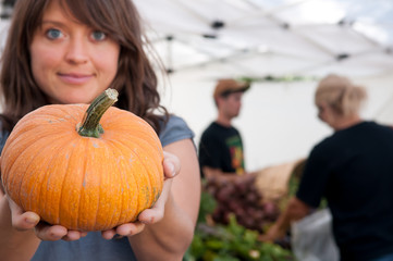 Wall Mural - Young woman hold a pumpkin at the farmers market