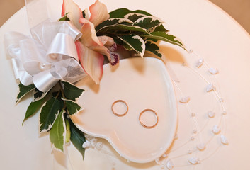 Wedding rings on the table with flowers closeup