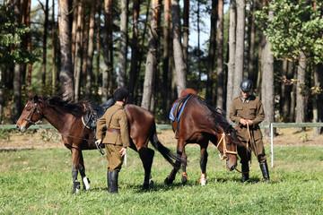 Dwóch żołnierzy z końmi na łące pod lasem.