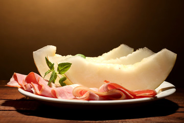 parma ham and melon, on wooden table, on brown background