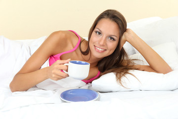 young beautiful woman with cup in bed