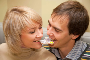 couple eating one cookie for two and looking eye to eye