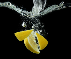 Deurstickers Opspattend water Sliced lemon in the water on black background