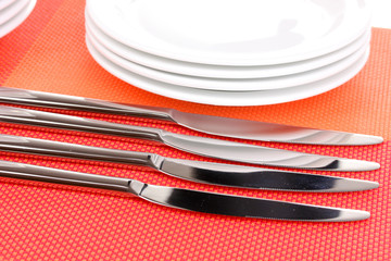 forks, knifes and spoons on red mat close-up