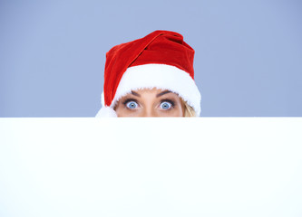Woman head and eyes with Santa hat above white board