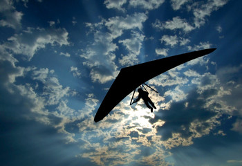 Hang glider silhouette on sky
