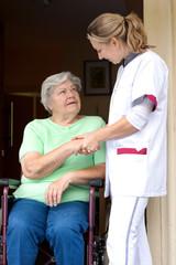 Pflegerin reicht Patientin im Rollstuhl die Hand