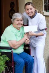 Pflegerin und Patientin im Rollstuhl halten gemeinsam einen Umsc