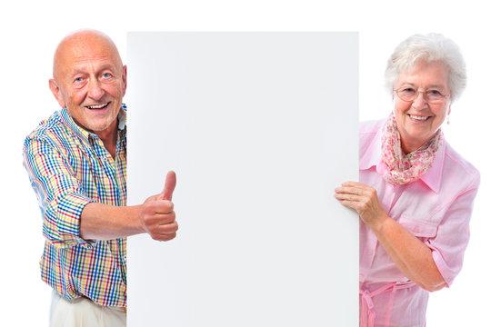 Seniorenpaar mit Werbeschild