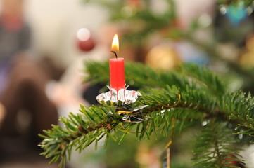 brennende Christbaumkerze auf einem Christbaumzweig 2