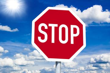 Stopschild mit blauem Himmel und Sonne