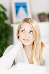 lächelnde blonde frau sitzt auf dem sofa