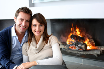 Romantic couple sitting by fireplace at home