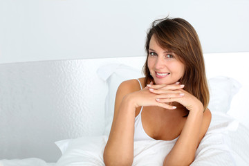 Portrait of attractive brunette girl sitting in bed