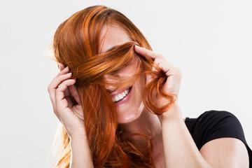 Hübsche Frau versteckt sich hinter Haarsträhne