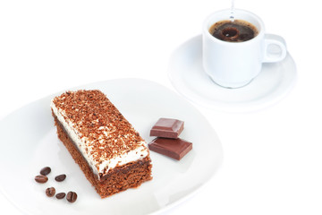 Breakfast of cake pieces of chocolate and coffee. On a white bac