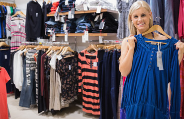 Woman holding up blue shirt in boutique