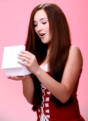 Young and beautiful christmas girl in red opening a gift