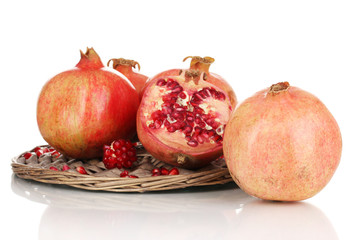 Ripe pomegranates on wicker cradle isolated on white