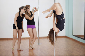 Pole fitness students taking pictures of their instructor
