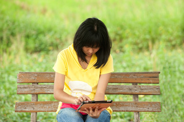 Pertty Asian young girl on tablet computer outside.