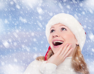happy funny girl in a Christmas hat on winter background