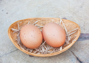 Two chicken eggs in bamboo basket