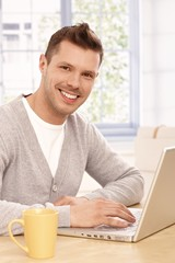 Portrait of young man with laptop