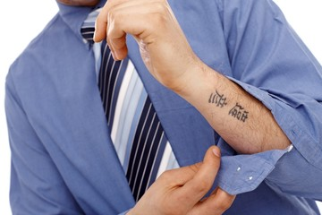 Body part of businessman with tattoo in forearm
