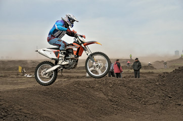 The motocross racer jumps by motorcycle
