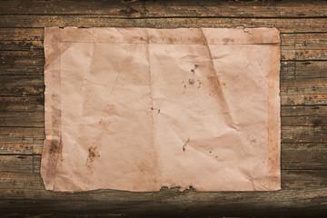 Vintage wrinkled paper on a faded wooden background